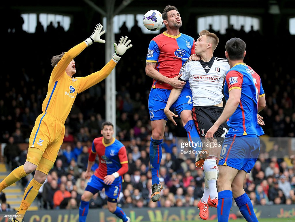 Damien Delaney of Crystal Palace leaps for the ball as Cauley Woodrow of Fulham challenges as his goalkeeper Wayne Hennessey waits to catch the ball during the Barclays Premier League match between Fulham and Crystal Palace at Craven Cottage on May 11, 2014 in London, England.