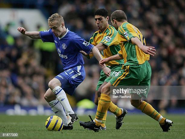 Damien Duff of Chelsea holds off Youssef Safri and Simon Charlton of Norwich during the Barclays Premiership match between Chelsea and Norwich City...
