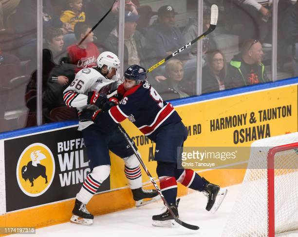 Damien Giroux of the Saginaw Spirit bodychecks Nico Gross of the Oshawa Generals during an OHL game at the Tribute Communities Centre on October 6,...