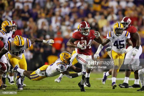 Damien Harris of the Alabama Crimson Tide avoids the tackle of Patrick Queen of the LSU Tigers in the second quarter of their game at Tiger Stadium...