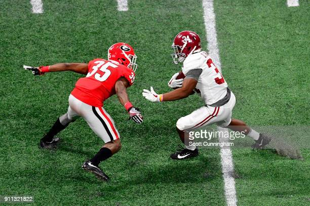 Damien Harris of the Alabama Crimson Tide carries the ball against Aaron Davis of the Georgia Bulldogs in the CFP National Championship presented by...