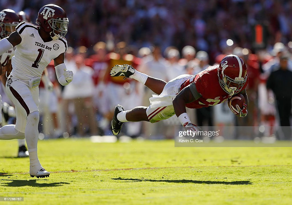 Damien Harris #34 of the Alabama Crimson Tide dives for more yardage away from Nick Harvey #1 of the Texas A&M Aggies at Bryant-Denny Stadium on October 22, 2016 in Tuscaloosa, Alabama.