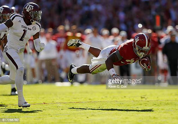 Damien Harris of the Alabama Crimson Tide dives for more yardage away from Nick Harvey of the Texas A&M Aggies at Bryant-Denny Stadium on October 22,...
