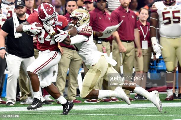 Damien Harris of the Alabama Crimson Tide is tackled by Derwin James of the Florida State Seminoles during their game at MercedesBenz Stadium on...