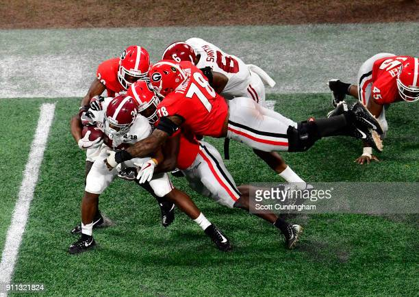 Damien Harris of the Alabama Crimson Tide is tackled by Roquon Smith J R Reed and D'Marcus Hayes of the Georgia Bulldogs in the CFP National...