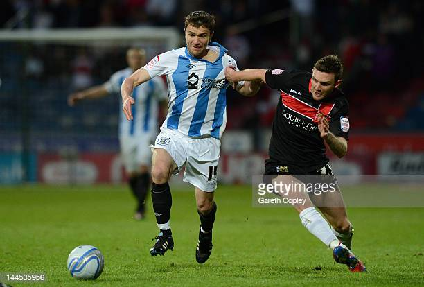 Damien Johnson of Huddersfield gets past Jay O'Shea of MK Dons during the npower League One Semi Final 2nd Leg match between Huddersfield Town and MK...
