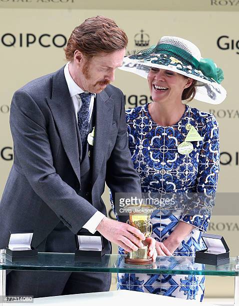 Damien Lewis and Helen McCrory joke about breaking a trophy they are about to present as they wait to present awards in the parade ring on day 1 of...