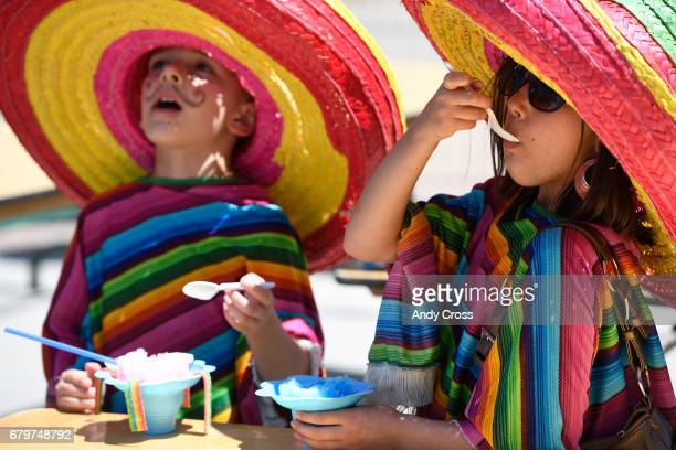 Damien Lopez left and his sister Ciara enjoy a frozen ice treat at the 30th annual Cinco de Mayo Celebrate Culture Festival May 6 2017 in Denver...