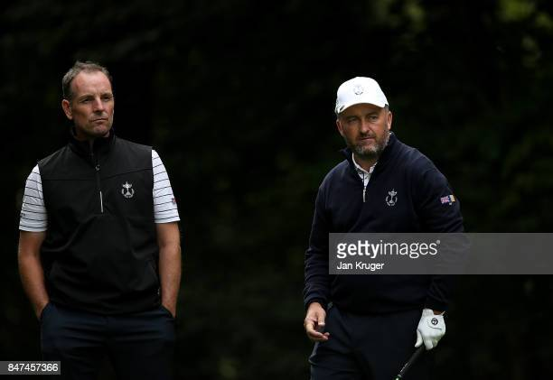 Damien McGrane and partner David Higgins of the Great Britain and Ireland PGA Cup team look on during the afternoon foursomes matches on day 1 of the...