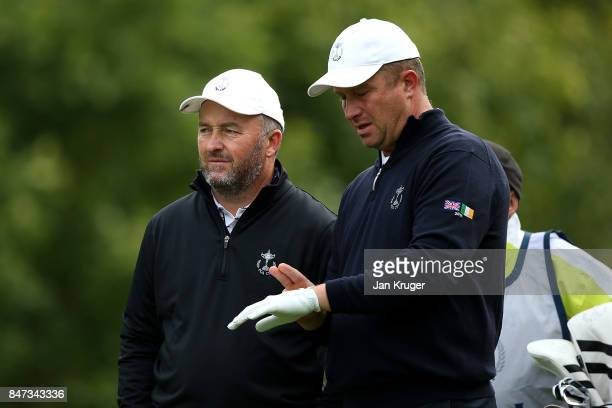 Damien McGrane of the Great Britain and Ireland PGA Cup team and partner Greig Hutcheon look on during the morning fouball matches on day 1 of the...