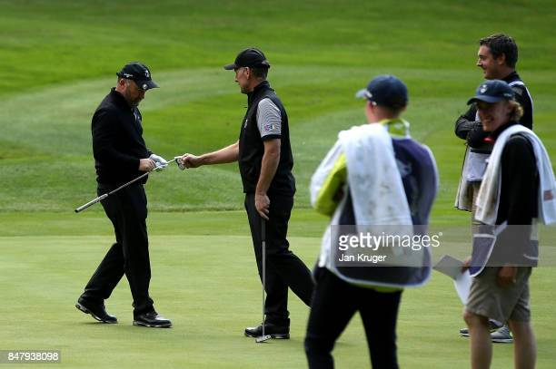 Damien McGrane of the Great Britain and Ireland PGA Cup team celebrates sinking a long range putt for birdie with playing partner David Higgins...