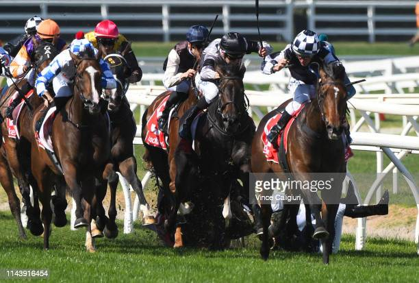 Damien Oliver riding Grinzinger Star winning Race 2 Bill Collins Handicap while Kayla Crowther riding Latin Beat is seen falling in the pack during...