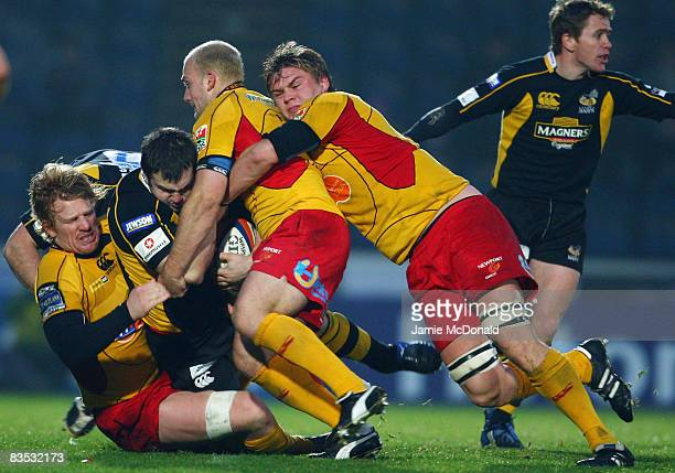 Damien Varley of Wasps is tackled by Jamie Ringer Richard Fussell and Ashley Smith of Newport Gwent Dragons during the EDF Energy Cup Group A match...