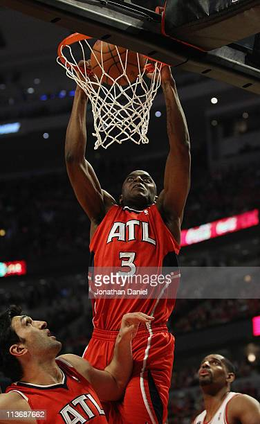 Damien Wilkins of the Atlanta Hawks dunks the ball over temmate Zaza Puchulia and Kurt Thomas of the Chicago Bulls in Game Two of the Eastern...