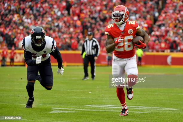 Damien Williams of the Kansas City Chiefs carries the ball for a touchdown over Jake Martin of the Houston Texans during the second quarter in the...