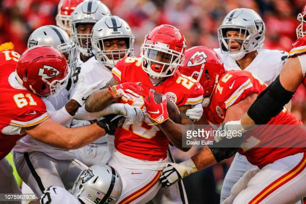 Damien Williams of the Kansas City Chiefs moves a pile of defenders in to the end zone for a touchdown during the first quarter of the game against...