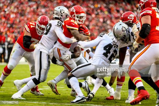 Damien Williams of the Kansas City Chiefs runs through a wall of defenders to score a touchdown during the first quarter of the game against the...