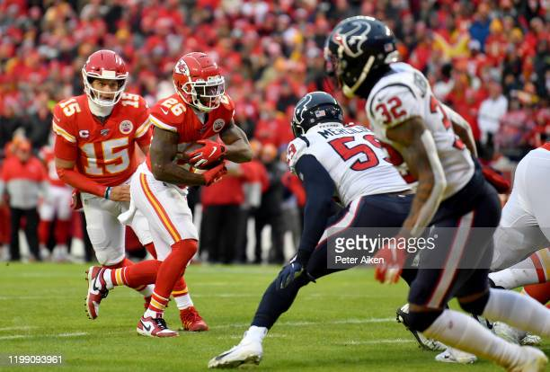 Damien Williams of the Kansas City Chiefs takes the hand off from quarterback Patrick Mahomes and rushes for a touchdown over the defense of the...