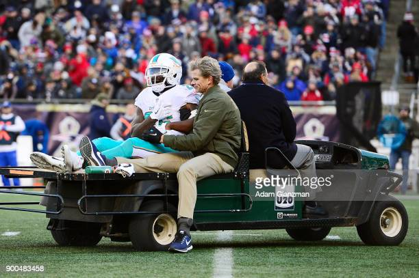 Damien Williams of the Miami Dolphins is carted off the field during a game against the New England Patriots at Gillette Stadium on November 26 2017...