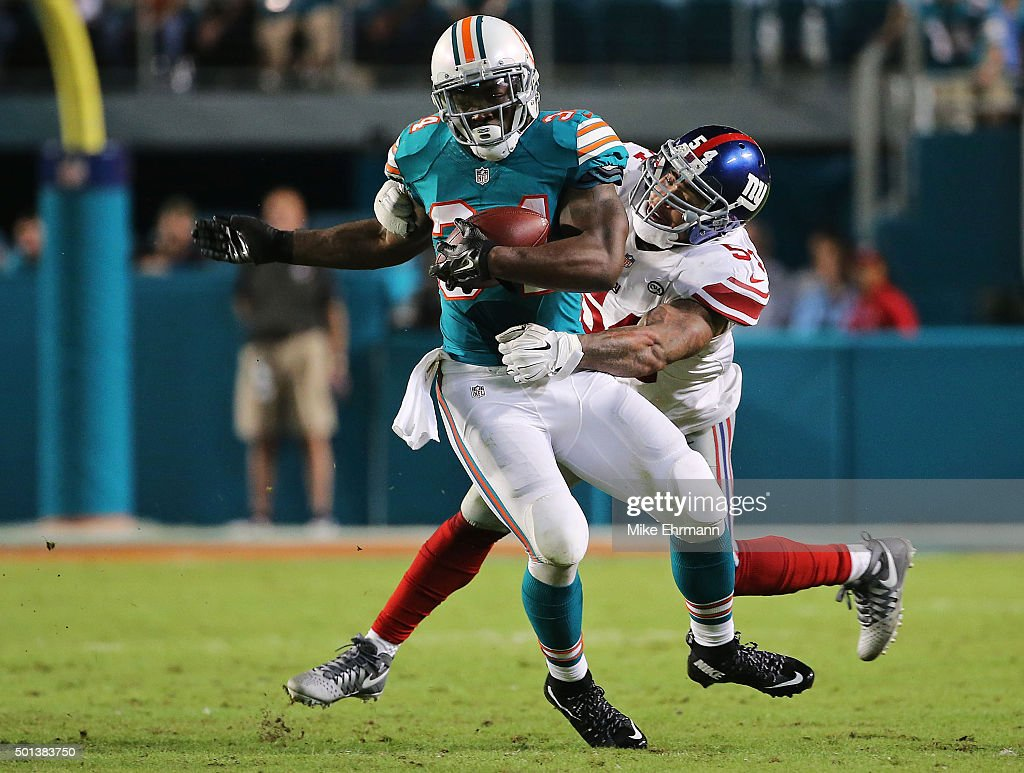 Damien Williams #34 of the Miami Dolphins is defended by Jonathan Casillas #54 of the New York Giants during the second half of the game at Sun Life Stadium on December 14, 2015 in Miami Gardens, Florida.