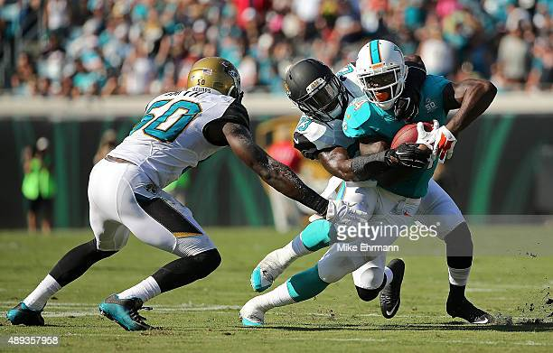 Damien Williams of the Miami Dolphins is tackled by James Sample of the Jacksonville Jaguars during a game at EverBank Field on September 20 2015 in...