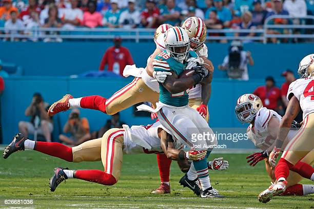 Damien Williams of the Miami Dolphins is tackled by Nick Bellore of the San Francisco 49ers as he runs with the ball on November 27, 2016 at Hard...