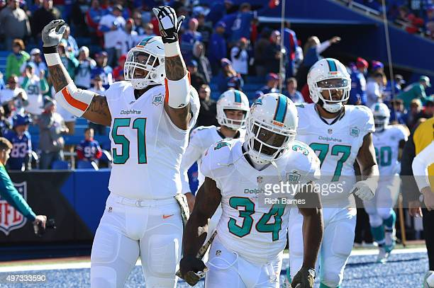 Damien Williams of the Miami Dolphins jogs onto the field as Mike Pouncey gestures to the crowd prior to the game against the Buffalo Bills at Ralph...