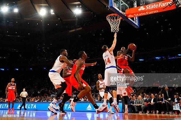 Damion James of the Washington Wizards attempts a shot under Jason Smith of the New York Knicks in a preseason game at Madison Square Garden on...