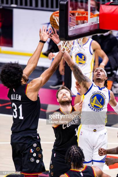 Damion Lee of the Golden State Warriors and Jarrett Allen of the Cleveland Cavaliers reach for a rebound during the third quarter at Rocket Mortgage...