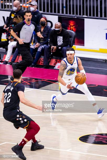 Damion Lee of the Golden State Warriors dribbles towards the basket during the third quarter of a game against the Cleveland Cavaliers at Rocket...