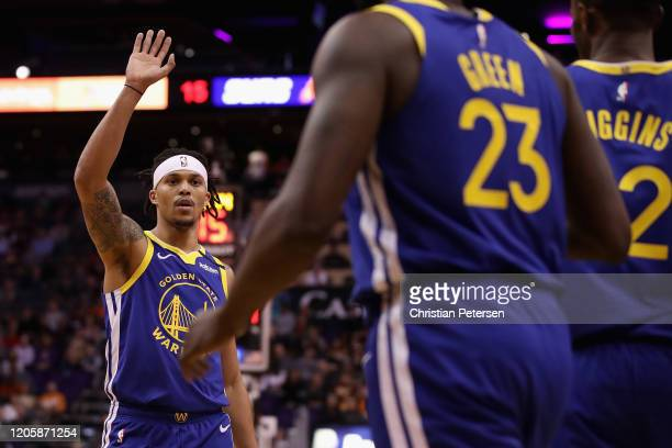 Damion Lee of the Golden State Warriors high fives Draymond Green after scoring against the Phoenix Suns during the first half of the NBA game at...