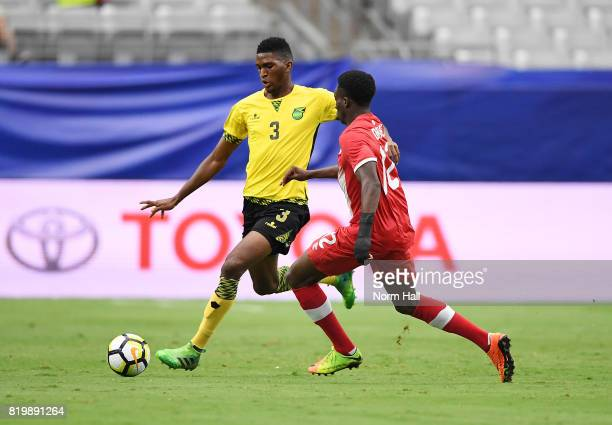 Damion Lowe of Jamaica brings the ball up field while being defended by Alphonso Davies of Canada during the first half in a quarterfinal match...