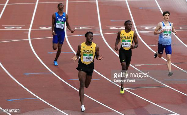 Damion Thomas of Jamaica celebrates as he crosses the line to win gold in the final of the men's 110m hurdles during the XX on day three of The IAAF...