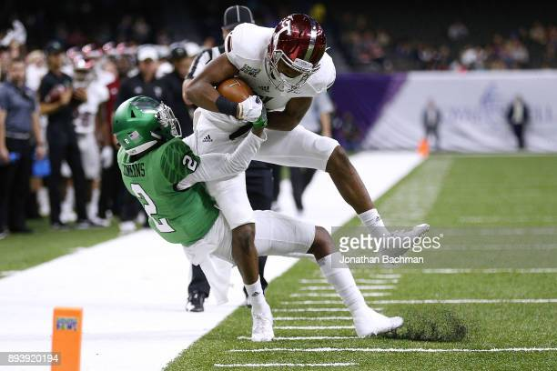 Damion Willis of the Troy Trojans is tackled by Eric Jenkins of the North Texas Mean Green during the first half of the RL Carriers New Orleans Bowl...