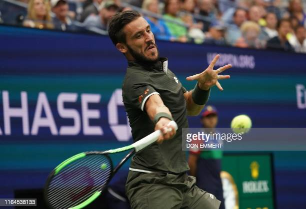 Damir Dzumhur of Bosnia and Herzegovina hits a return to Roger Federer of Switzerland during the second round of the men's 2019 US Open tennis...