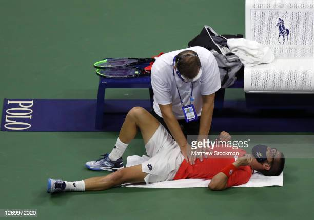 Damir Dzumhur of Bosnia and Herzegovina is worked on by trainer Clay Snitenan during his Men's Singles first round match against Novak Djokovic of...