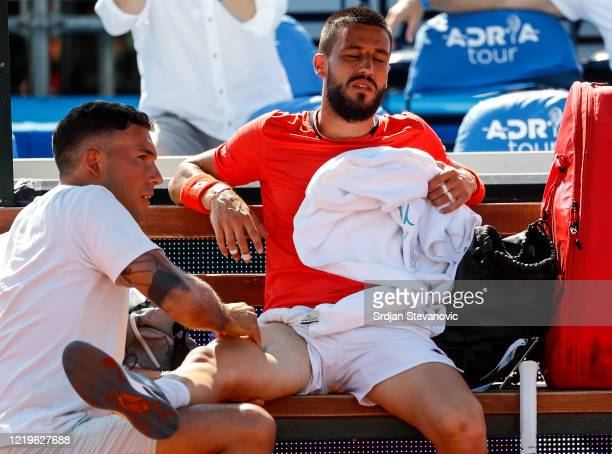 Damir Dzumhur of Bosnia and Herzegovina receives medical treatment during his match against Dominic Thiem during the Adria Tour charity exhibition...