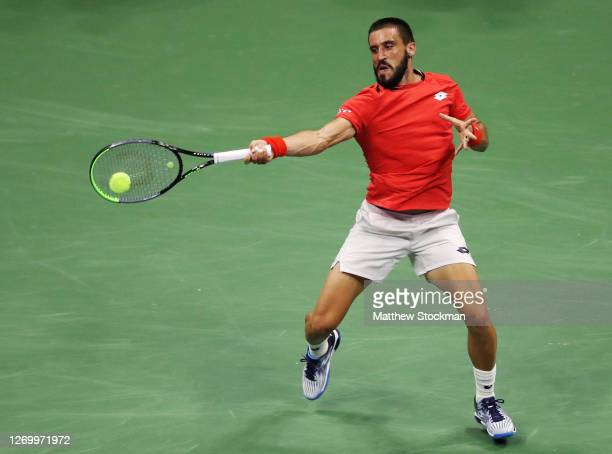 Damir Dzumhur of Bosnia and Herzegovina returns a volley during his Men's Singles first round match against Novak Djokovic of Serbia on Day One of...