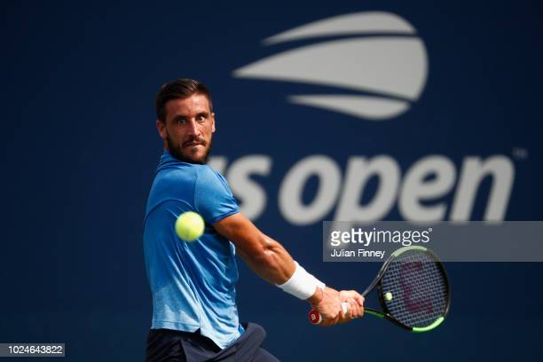 Damir Dzumhur of Bosnia and Herzegovina returns the ball in his mens singles first round match against Dusan Lajovic of Servia on Day One of the 2018...