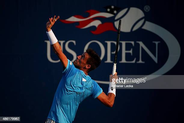 Damir Dzumhur of Bosnia and Herzegovina serves against Bernard Tomic of Australia during their Men's Singles First Round match on Day Two of the 2015...