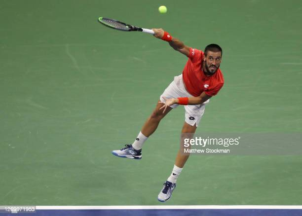 Damir Dzumhur of Bosnia and Herzegovina serves during his Men's Singles first round match against Novak Djokovic of Serbia on Day One of the 2020 US...