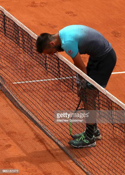 Damir Dzumhur of Bosnia and Herzegovinia bites the net in frustration during his mens singles third round match against Alexander Zverev of Germany...
