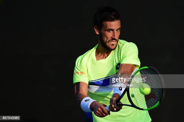 Damir Dzumhur of Bosnia returns a shot from Gilles Simon of France during the fourth day of the WinstonSalem Open at Wake Forest University on August...