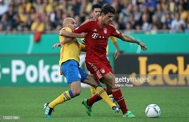 Damir Vrancic of Braunschweig and Mario Gomez of Muenchen battle for the ball during the DFB Cup first round match between Eintracht Braunschweig and...