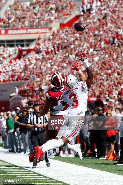 Damon Arnette of the Ohio State Buckeyes and Peyton Hendershot of the Indiana Hoosiers jump for the ball at Memorial Stadium on September 14 2019 in...