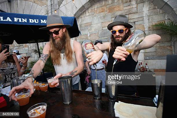 Damon Boelte and Ehren Shorday mix drinks during The 7th Annual Saveur Summer Cookout at Boat Basin Cafe on June 21 2016 in New York City