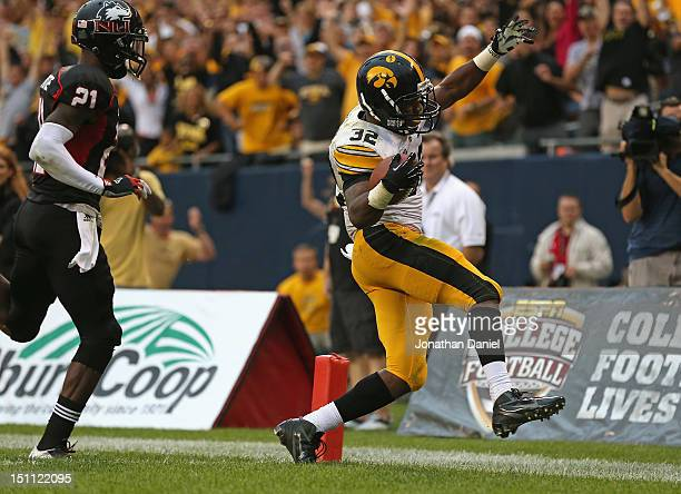 Damon Bullock of the Iowa Hawkeyes scores the gamewinning touchdown in front of Dechane Durante of the Northern Illinois Huskies at Soldier Field on...