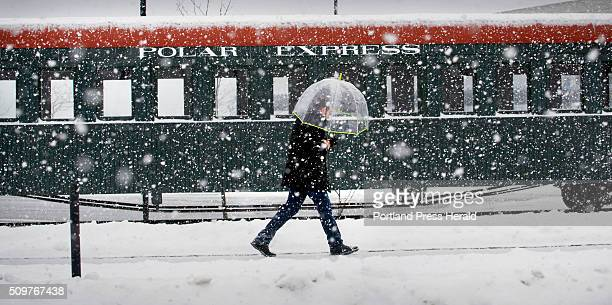 Damon Fitt of Portland walks past a narrow gauge railroad car on his way to work on Thursday February 11 as heavy snow falls in the city