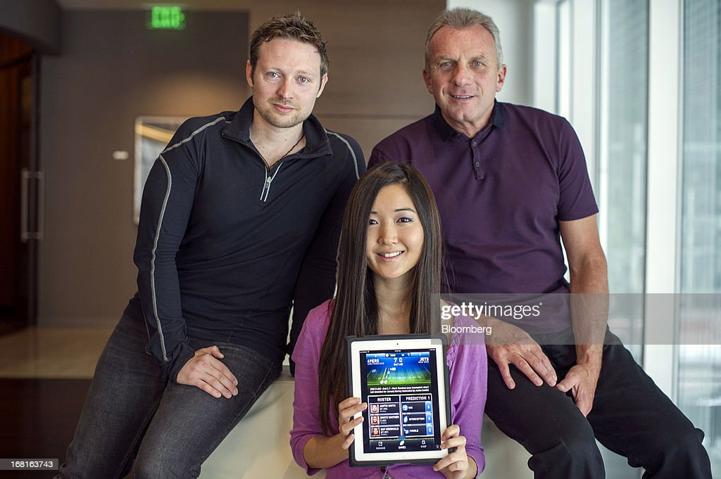 Damon Grow, co-founder of iMFL, left, and Joseph 'Joe' Montana, co-founder of iMFL and retired National Football League (NFL) quarterback, right, and Jane Chung, product manager for iMFL, holding an Apple Inc. iPad with the iMFL game displayed, sit for a photograph after an interview in San Francisco, California, U.S. on Tuesday, April 30, 2013. iMFL, a fantasy football application that will be available for download at the Apple Inc. App Store, will be released before the start of the 2013 NFL season. Photographer: David Paul Morris/Bloomberg via Getty Images