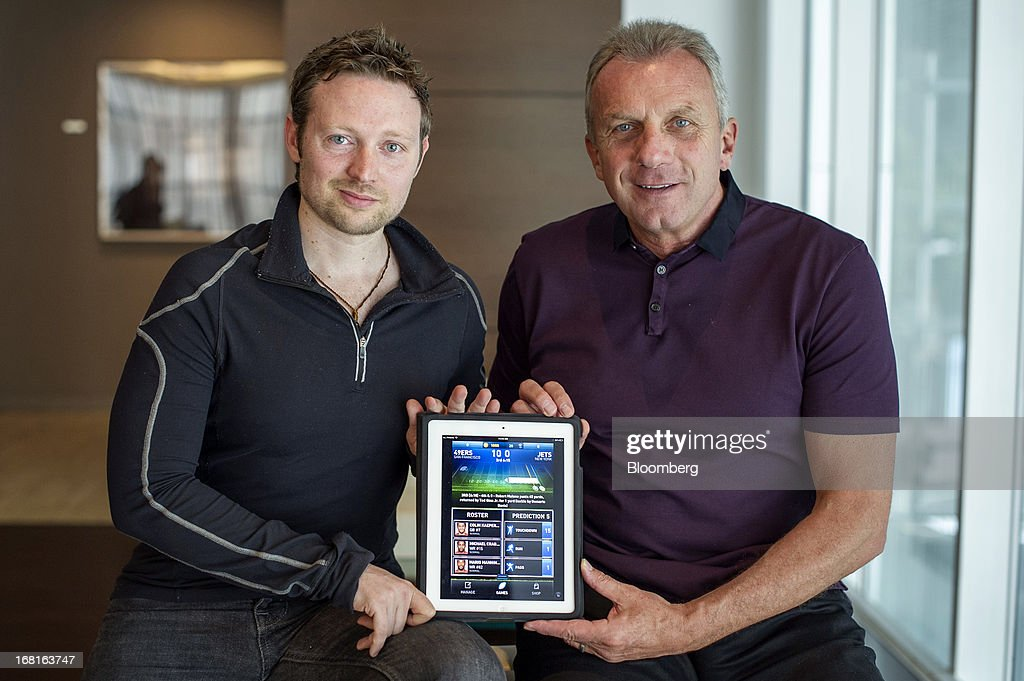 Damon Grow, co-founder of iMFL, left, and Joseph 'Joe' Montana, co-founder of iMFL and retired National Football League (NFL) quarterback, hold an Apple Inc. iPad with the iMFL game displayed as they sit for a photograph after an interview in San Francisco, California, U.S. on Tuesday, April 30, 2013. iMFL, a fantasy football application that will be available for download at the Apple Inc. App Store, will be released before the start of the 2013 NFL season. Photographer: David Paul Morris/Bloomberg via Getty Images